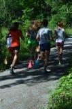 Hintere Ansicht von den Jugendlichen, die auf Weg 2 laufen Stockfoto