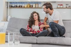 Hintere Ansicht von den jungen Paaren, die sich amüsieren und auf dem Sofa im Wohnzimmer fernsehen Junger Mann und Frau lizenzfreie stockfotografie