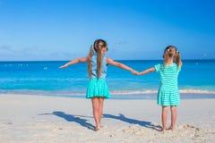 Hintere Ansicht von den kleinen Mädchen, die Sommer genießen, setzen auf den Strand Lizenzfreie Stockfotografie