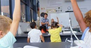 Hintere Ansicht von den Mischrasseschulkindern, die Hände im Klassenzimmer 4k anheben stock footage