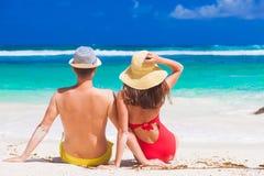 Hintere Ansicht von den Paaren, die auf einem tropischen Strand auf Mahe, Seychellen sitzen Stockbilder