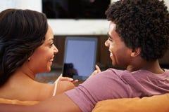 Hintere Ansicht von den Paaren, die auf Sofa Using Digital Tablet sitzen Lizenzfreie Stockbilder