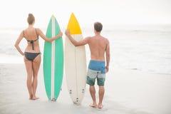 Hintere Ansicht von den Paaren, die mit einem Surfbrett auf dem Strand stehen Lizenzfreies Stockbild