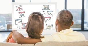 Hintere Ansicht von den Paaren, die verschiedene Ikonen auf Arbeitsplatzrechner beim zu Hause sitzen betrachten Lizenzfreie Stockfotografie