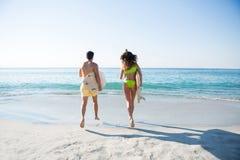 Hintere Ansicht von den Paaren, die zusammen beim Halten von Surfbrettern am Strand laufen Stockfotografie