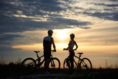 Hintere Ansicht von den Paarradfahrern, die mit Fahrrädern stehen und den Sonnenuntergang genießen Lizenzfreies Stockfoto