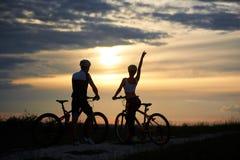 Hintere Ansicht von den Paarradfahrern, die mit Fahrrädern stehen und den Sonnenuntergang genießen Stockfotografie