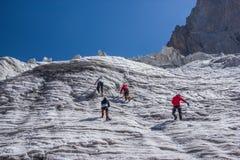 hintere Ansicht von den Wanderern, die am schönen Schnee klettern, bedeckte Berge, Kirgisistan mit einer Kappe, stockfotos