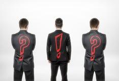 Hintere Ansicht von drei Geschäftsmännern mit Fragezeichen und Ausruf eins in der Mitte Stockfotografie
