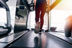 Hintere Ansicht von Füßen mit Turnschuhen des weiblichen Läufers/des Rüttlers, die zuhause auf Tretmühle in Aktion laufen stockbild