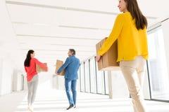 Hintere Ansicht von Geschäftsleuten mit den Pappschachteln, die in neues Büro sich bewegen Stockfotos