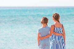 Hintere Ansicht von girlson zwei das Strandhintergrund-Blaumeer Stockbild