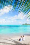 Hintere Ansicht von kleinen Mädchen auf sandigem Strand Glückliche Kinder, die unter der Palme auf tropischem Strand sitzen Lizenzfreie Stockbilder