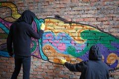 Hintere Ansicht von Männern mit Haube gegen Wand mit Graffiti Lizenzfreies Stockbild