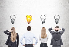 Hintere Ansicht von Männern und von Frauen mit Glühlampen Lizenzfreie Stockfotos