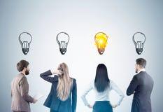 Hintere Ansicht von Männern und von Frauen mit Glühlampen, getont Lizenzfreies Stockbild