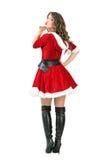 Hintere Ansicht von sexy attraktiver junger weiblicher Santa Claus, die einen Kuss an der Kamera durchbrennt Lizenzfreies Stockfoto