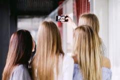 Hintere Ansicht von vier Mädchen, die selfie tun stockfotografie