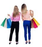 Hintere Ansicht von zwei Frauen mit Einkaufstaschen Stockbilder
