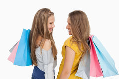 Hintere Ansicht von zwei jungen Frauen mit Einkaufenbeuteln Lizenzfreie Stockfotos