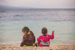 Hintere Ansicht von zwei kleinen Mädchen, die nahe dem Meer sitzen Stockfotografie
