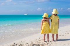Hintere Ansicht von zwei kleinen netten Mädchen, die das Meer auf weißem Strand betrachten Stockfotografie