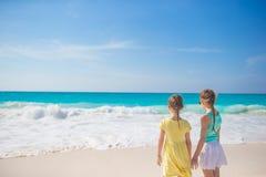 Hintere Ansicht von zwei kleinen Schwestern auf weißem Strand Lizenzfreie Stockfotos
