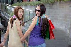 Hintere Ansicht von zwei Schönheitsfrauen, die den Spaß habend zusammenhält Einkaufstaschen gehen stockfotografie