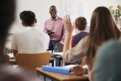 Hintere Ansicht weiblicher Student-Asking Question In-Klasse stockfotos