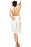 Hintere Ansichtfrau eingewickelt im Tuch, das zurück sie berührt lizenzfreie stockfotos