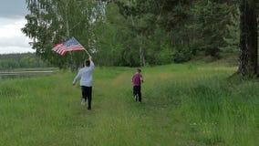 Hintere Ansichtkinder, die mit der US-Flagge laufen stock video