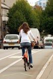 Hintere Frau, die ein Fahrrad in der Stadt reitet stockfoto