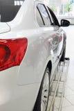 Hintere rote Lichter des neuen weißen glänzenden Autos, das im Büro steht Lizenzfreies Stockbild