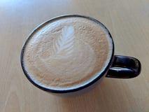 Hintere Schale Cappuccino auf Untertasse mit einem Blattmuster im Schaum lizenzfreies stockfoto