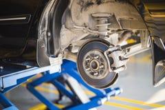 Hintere Scheibenbremse auf Auto im Prozess des geschädigten Reifenersatzes Stockbilder