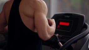 Hintere und Seitenansicht eines starken Bodybuilders, der auf einer Tretmühle beim Ausarbeiten in der Turnhalle läuft Gesunder Le stock footage
