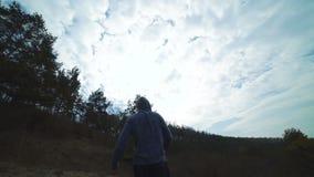 Hinterer Blick des Mannes zurück gehend auf den Wald-` s Rasen und dem Boxen langsam stock video