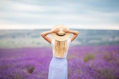 Hinteres Ansichtmädchen auf dem purpurroten Lavendelfeld, Sommerzeit Lizenzfreie Stockfotografie