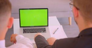Hinteres Ansichtporträt der Nahaufnahme von zwei erfolgreichen Geschäftsmännern, die zuhause Laptop mit grünem Schirm im Büro ver stock video footage