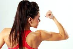 Hinteres Ansichtporträt einer jungen Sportfrau, die ihr Bizeps betrachtet Lizenzfreie Stockfotos