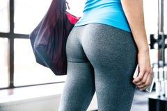 Hinteres Ansichtporträt einer jungen Frau mit Tasche und Smartphone Stockfotos
