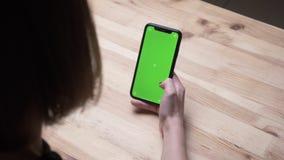 Hinteres Ansichttrieb der Nahaufnahme der weiblichen Hand ein Telefon mit gr?nem Farbenreinheitsschirm auf dem Schreibtisch im B? stock footage