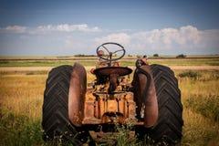 Hinteres Ende eines rostigen alten Traktors, der Landwirtschaftslandschaft gegenüberstellt Stockfotografie