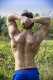 Hinteres ofYoung muskulöser hemdloser Mann in der Natur Stockfoto