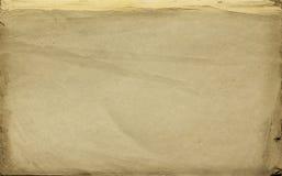 Hintergrund als alte Papierbeschaffenheit mit Alterskennzeichen im gelben Schatten Lizenzfreie Stockbilder