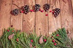 Hintergrund auf roten berrys und Fichte des alten Holztischs Lizenzfreie Stockfotos