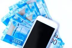 Hintergrund Banknotenwährungsroubleand und -Handys des Geldes des russischen im Nennwert von zwei tausend Neue Kartenbank Russlan stockfotografie