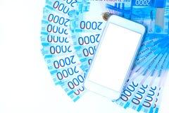 Hintergrund Banknotenwährungsroubleand und -Handys des Geldes des russischen im Nennwert von zwei tausend Neue Kartenbank Russlan lizenzfreie stockfotos