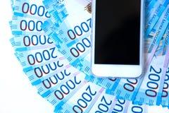 Hintergrund Banknotenwährungsroubleand und -Handys des Geldes des russischen im Nennwert von zwei tausend Neue Kartenbank Russlan stockbild