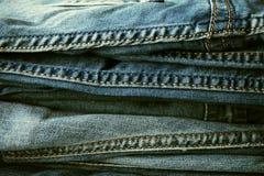 Hintergrund, Beschaffenheit eines Stapels der modischen Jeanshosen lizenzfreie stockfotos